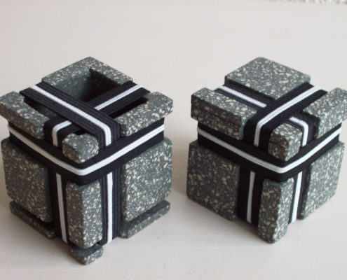 Two square stoneware cubes with nine elastics each.